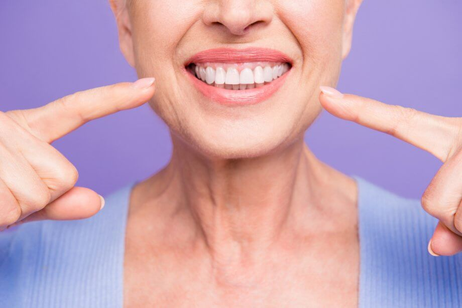 Woman Pointing To Her Smile And Healthy Teeth